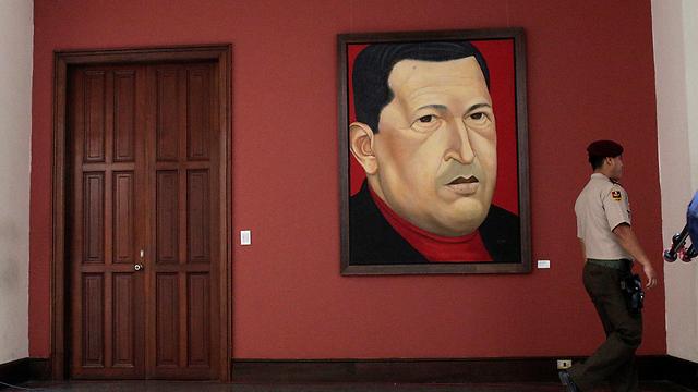 איש המשמר הלאומי על רקע ציור של המנהיג המנוח הוגו צ'אבס (צילום: רויטרס)
