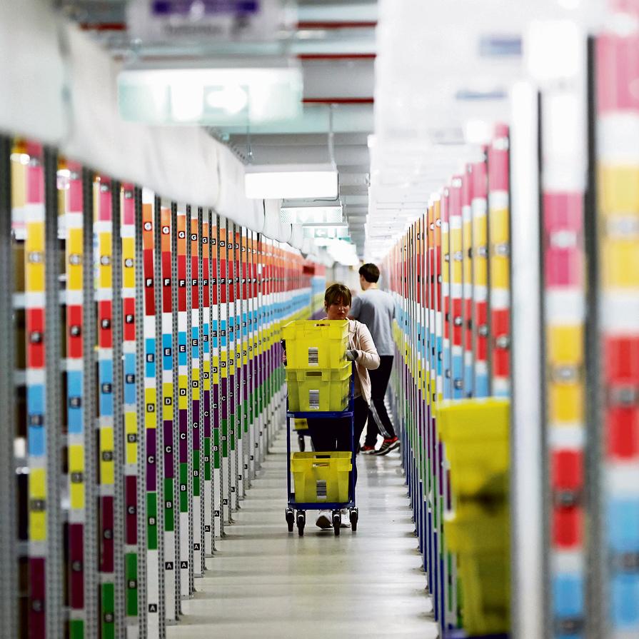 מחסן ספרים של אמזון בגרמניה. בזוס יכול לאכול צהריים עם העובדים בחדר האוכל, אבל אין לו בעיה גם לצעוק על אחד מהם לעיני כולם   צילום: אי.פי.איי