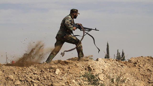 Shiite fighter clashes with members of the Sunni-dominated Free Syrian Army, in Hatita, Syria (Photo: AP)