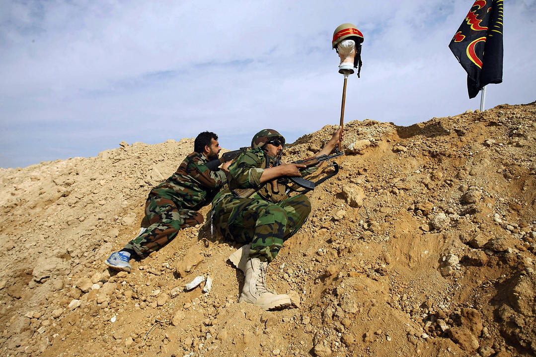 Iraqi and Lebanese Shiite fighters from the Hussein Brigade use a helmet to draw sniper fire, during clashes with the Sunni-dominated Free Syrian Army, in Hejeira, Syria (Photo: AP)