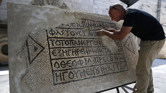 A conservationist working on the mosaic (Photo: AFP)