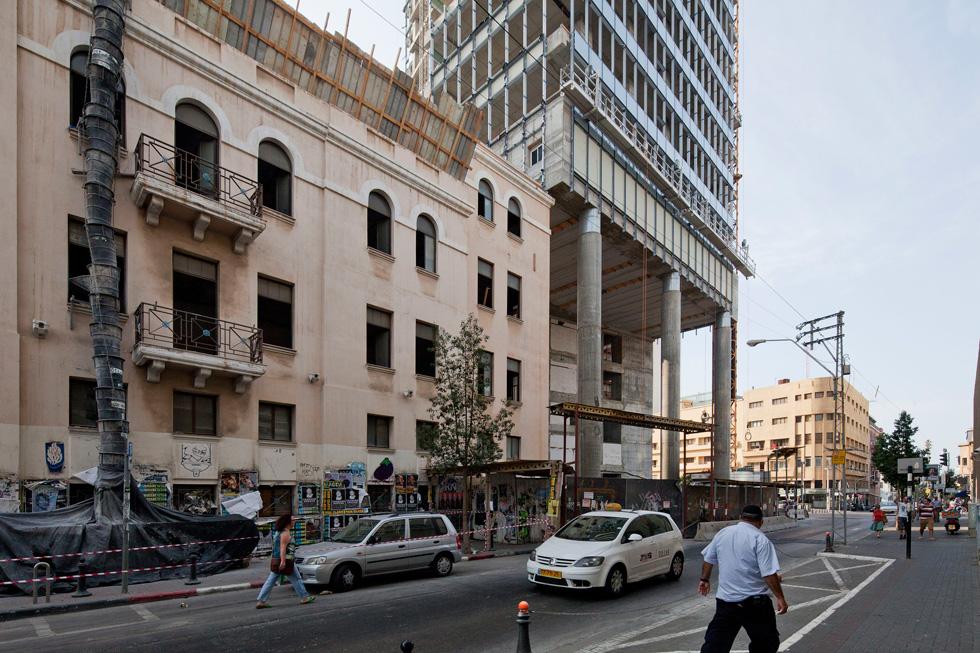 המגדל בזמן ההקמה. עוד שמונה קומות נוספו לו במרוצת האישורים, בשעה שהציבור קיבל בריכת שיקוף ליד קפה ארומה (צילום: אביעד בר נס)