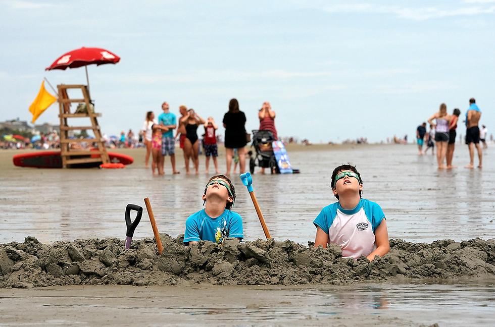 """ילדים צופים בליקוי החמה בדרום קרוליינה, ארה""""ב (צילום: AFP)"""