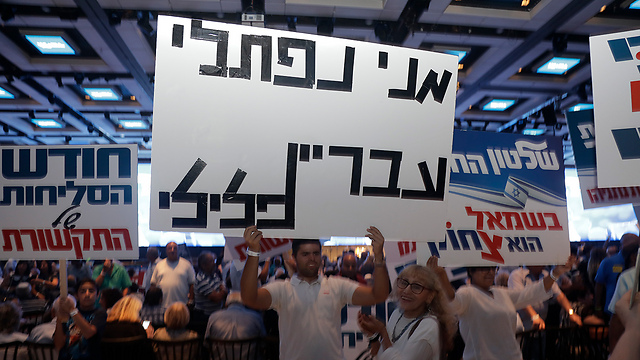 Netanyahu supporters at Wednesday's rally, with a sign that reads, 'Meni Naftali is a criminal' (Photo: Shaul Golan)