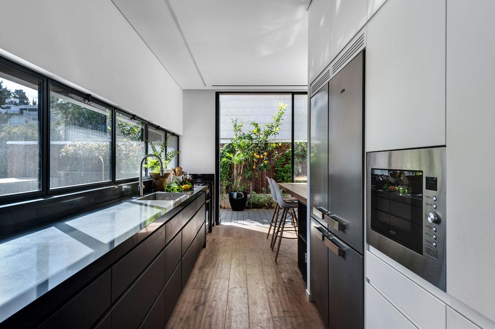 במטבח הזה מגיעים לכל הפונקציות החשובות – מקרר, תנור, כיריים וכיור – מבלי לזוז, בתנועה מינימלית (צילום: עודד סמדר)