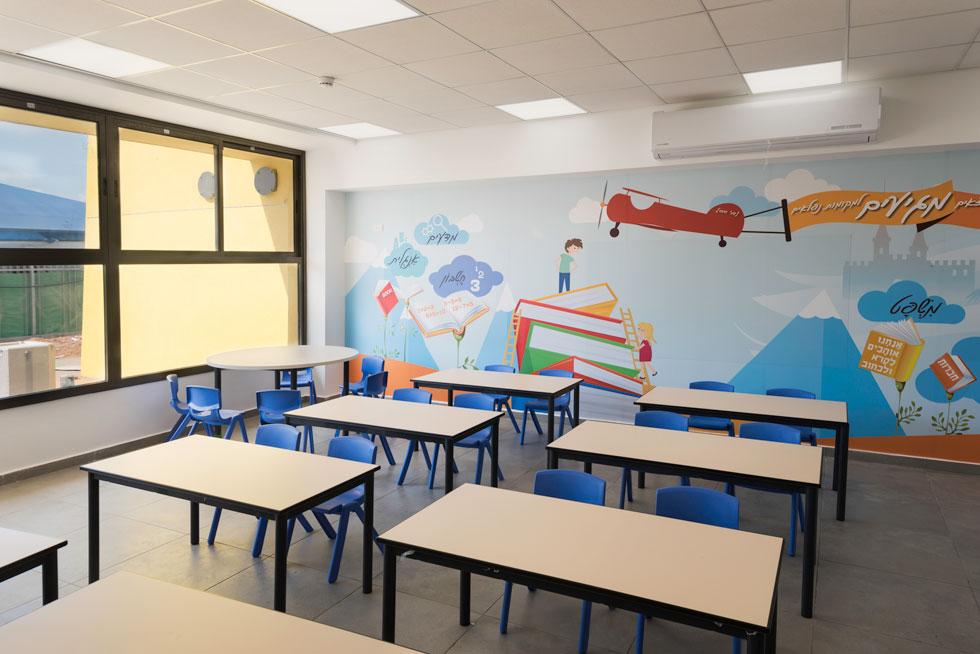 """כיתות הלימוד סטנדרטיות. על הקיר האחורי בכל אחת מהן מופיע איור גדול. בכיתות א' נלווה אליו שיר הילדים הנצחי """"והילד הזה הוא אני"""" של יהודה אטלס (צילום: ליאור גרונדמן)"""