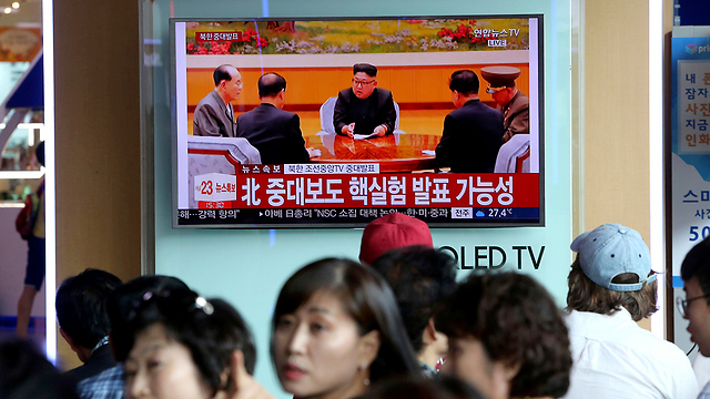 תושבים חולפים על פני מסך טלוויזיה בדרום קוריאה, ובו משודרים עדכונים על הניסוי הצפון קוריאני (צילום: AP)