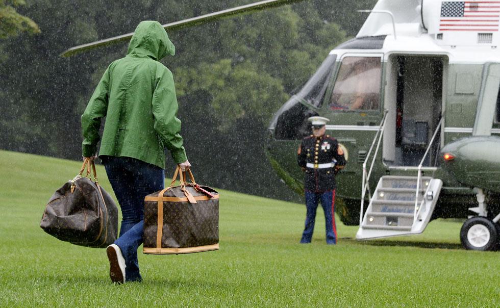 עדשות המצלמות אף לכדו מאחורי בני הזוג העולים למטוס דמות נוספת, שאחזה בכל יד תיק נשיאה גדול של לואי ויטון, שמחירו הממוצע הוא 4,000 דולר לאחד (צילום: GettyImages)