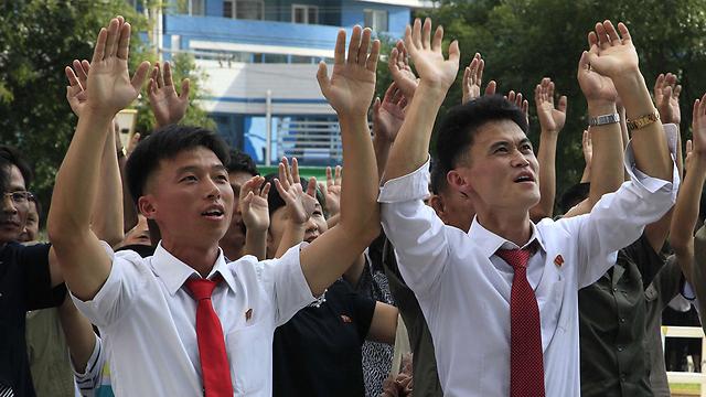 אזרחים צפון קוריאנים מריעים עם פרסום ההודעה על הניסוי הגרעיני (צילום: AP)