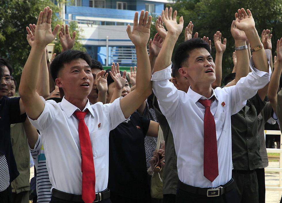 אזרחים צפון קוריאנים חוגגים את הניסוי בפצצת המימן (צילום: AP)