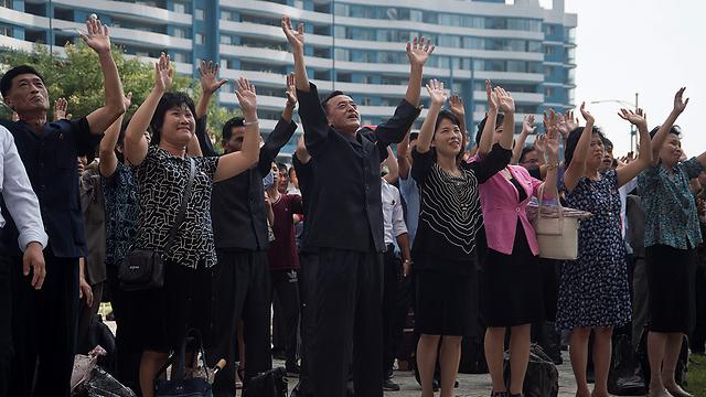 """חגגו את """"הניסוי המוצלח"""". תושבים בפיונגיאנג, בירת צפון קוריאה (צילום: AFP)"""