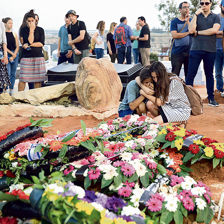 Crying on the graves, after the attack (Photo: Tal Shahar)