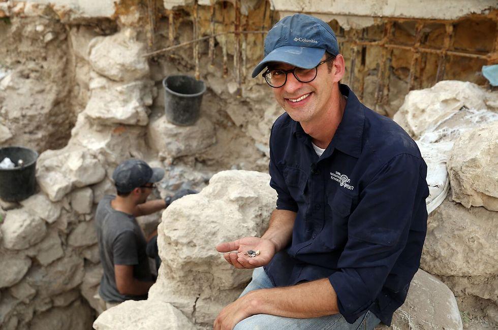 """ד""""ר ג'ו עוזיאל עם הבולות שנחשפו בעיר דוד (צילום: אליהו ינאי, עיר דוד)"""