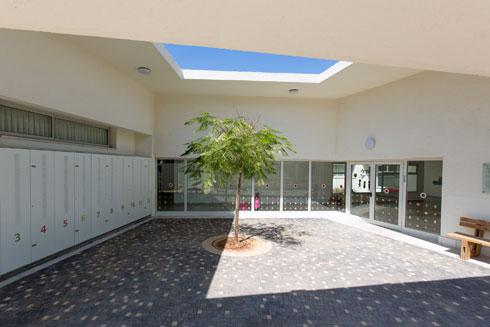 רחבת הכניסה המרוצפת, ומשמאל: תאי האחסון האישיים של הילדים (צילום: דור נבו)