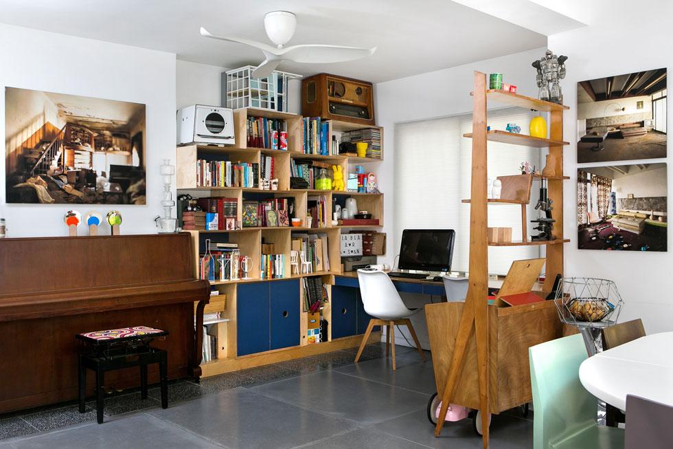 פינת העבודה והנגינה מופרדת מהסלון בעזרת ספריית וינטג'. ''רצינו שהכל יהיה פתוח, יחד'', מסבירה שרפשטיין. ''יש בבית מחשב אחד וטלוויזיה אחת ותקוותינו שזה יישאר ככה אז חולקים''. שלושת הצילומים שמעל הפסנתר ולצד הספרייה הם מסדרת המלונות הנטושים של אוהד מטלון (צילום: שירן כרמל)