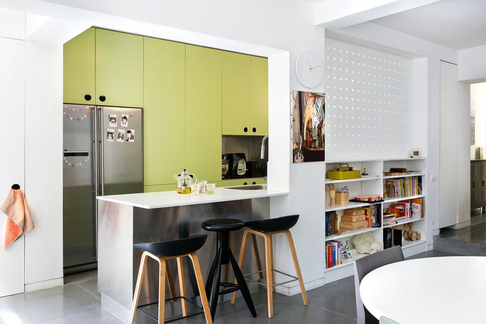 צבע ירוק מרגיע נבחר לארונות המטבח, שמבנהו צר וארוך, אילוץ של המרחב. מחיצה מחוררת מפרידה בין בין הכיריים ומשטח העבודה לכניסה ופינת העבודה. שרפשטיין מתכננת להשחיל בחורים מוטות עגולים, שישמשו לתלייה (צילום: שירן כרמל)
