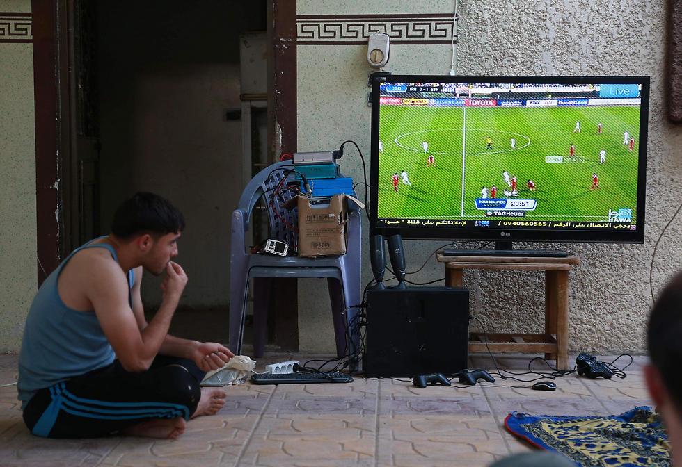 אוהד סורי המתגורר באזור שבשליטת המורדים צופה במשחק (צילום: AFP) (צילום: AFP)