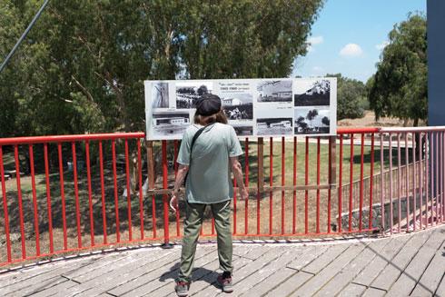 האוצרת דליה בר אמוץ על רקע תערוכת הצילומים שאצרה בנחל אלכסנדר, קרוב למשק, ובה צילומים היסטוריים של המוסד החינוכי רמות חפר (צילום: ליאור גרונדמן)