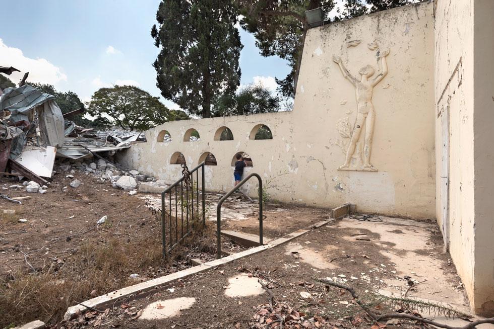 האדריכל בנה קיר עם חורי הצצה מקושתים, שהזמינו את בני ובנות הנוער להצצה ומשחק, ועל הקיר תבליט של הפסל הנודע נתן רפופורט (צילום: ליאור גרונדמן)