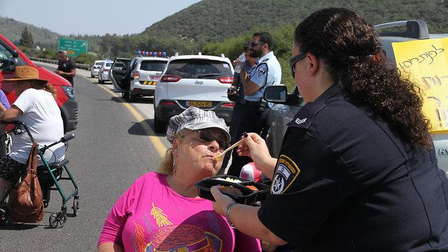 Police Sergeant Neta Shema feeds disabled protestor Iris Haya Zigdon (Photo: Zohar Shahar)