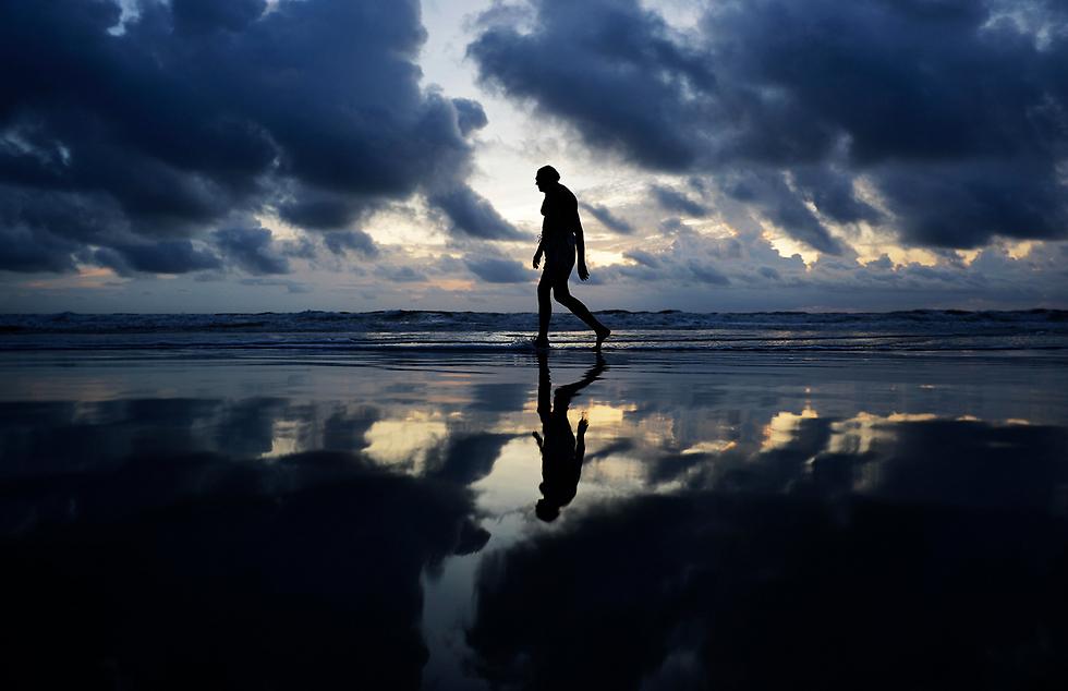"""צעידה ליד הים לפני הגעת ההוריקן """"אירמה"""" בדייטונה ביץ', פלורידה (צילום: AP)"""