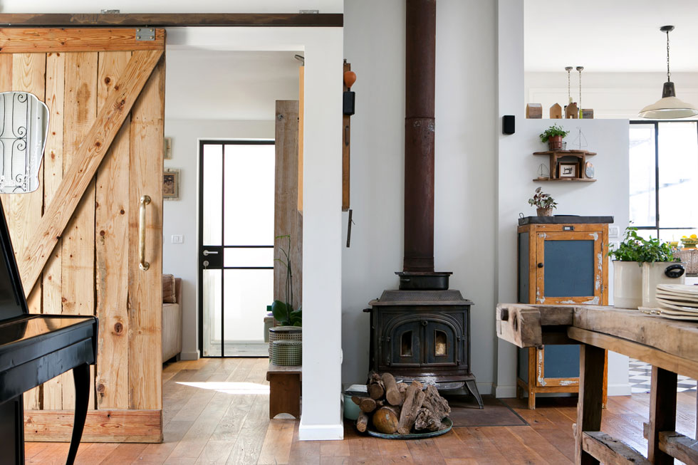 קמין העצים שניצב בפינת החלל המרכזי של הבית מחמם גם את הקומה השנייה. דלת חדר העבודה (משמאל) היא  דלת אסם ישן, שהותאמה מחדש (צילום: שירן כרמל)
