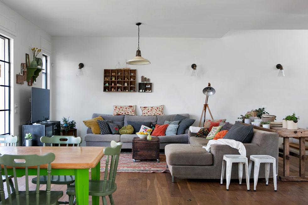 פינת הישיבה מוגדרת באמצעות שטיח. על הקיר תלוי אוסף המיניאטורות של בעלת הבית בכוורת עץ (צילום: שירן כרמל)