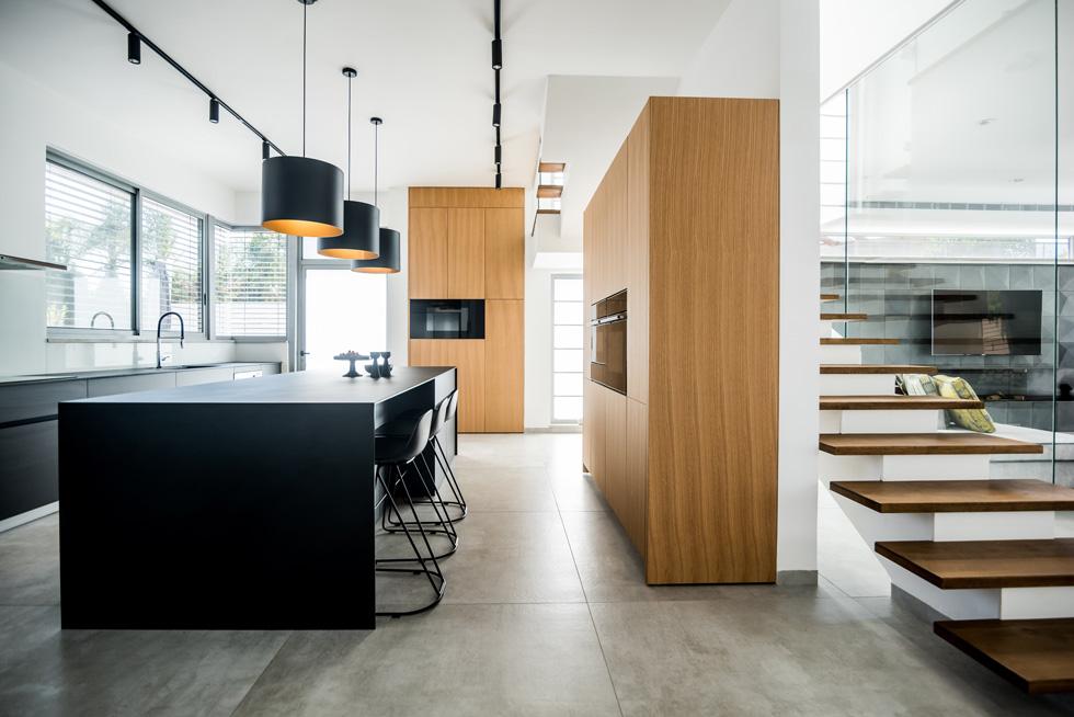 המטבח בשחור-פחם עם אי רחב ידיים (3.3 מטר אורכו) ודומיננטי בעיצובו  (צילום: גלעד רדט, סטיילינג צילומים: לינוי לנדאו)