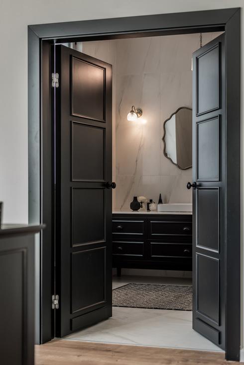 גולת הכותרת היא דלת שחורה דו כנפית בסגנון קלאסי המובילה לחדר הרחצה, שאף הוא מאופיין בטון שחור דומיננטי, לצד שיש לבן עם גידים אפורים (צילום: גלעד רדט, סטיילינג צילומים: לינוי לנדאו)