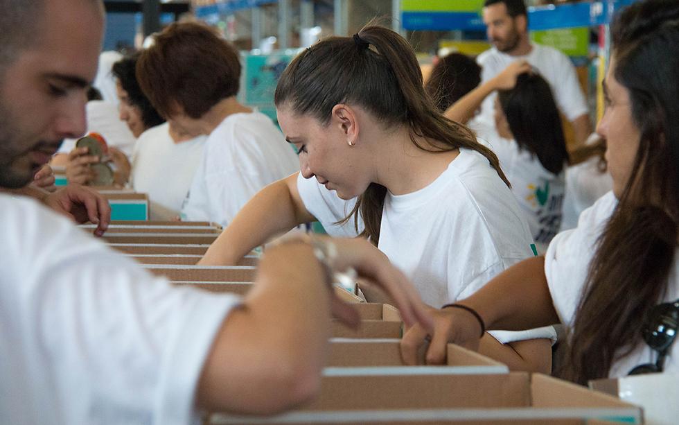מתנדבים אורזים מזון במחסני ארגון לתת ()