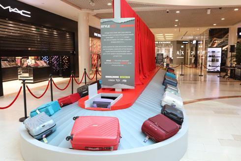 התערוכה בקניון רמת אביב, המשלבת מסוע מזוודות יחד עם הצילומים מלוח השנה (צילום: רפי דלויה)