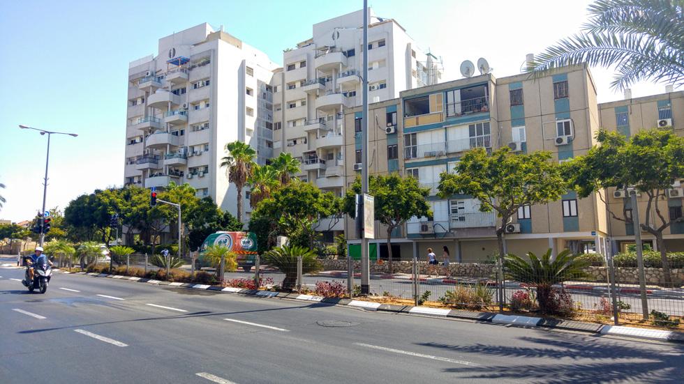 ''כפר שלם'' הוא יותר עיירה, שמחולקת לשכונות. בצמד הבניינים הזה מתגוררת הכותבת: היא המירה דירת 50 מטרים רבועים בשיכון שלו וקטן בצד השני והמטופח של העיר בדירת ארבעה וחצי חדרים, בקומה השביעית של בניין בן 36 דירות ומעלית אחת. מהסלון רואים את המטוסים ממריאים מנתב''ג (צילום: חנה קלדרון)