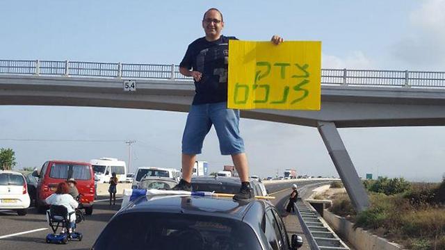 מפגין במהלך חסימת כביש החוף באזור זכרון יעקב (צילום: ''הנכים הופכים לפנתרים'')