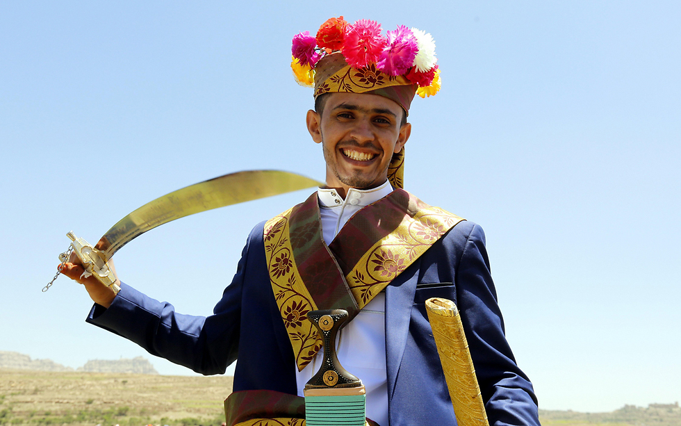 חתן בלבוש מסורתי, עם חרב, בטקס חתונה המוני ל-120 זוגות בתימן (צילום: EPA)