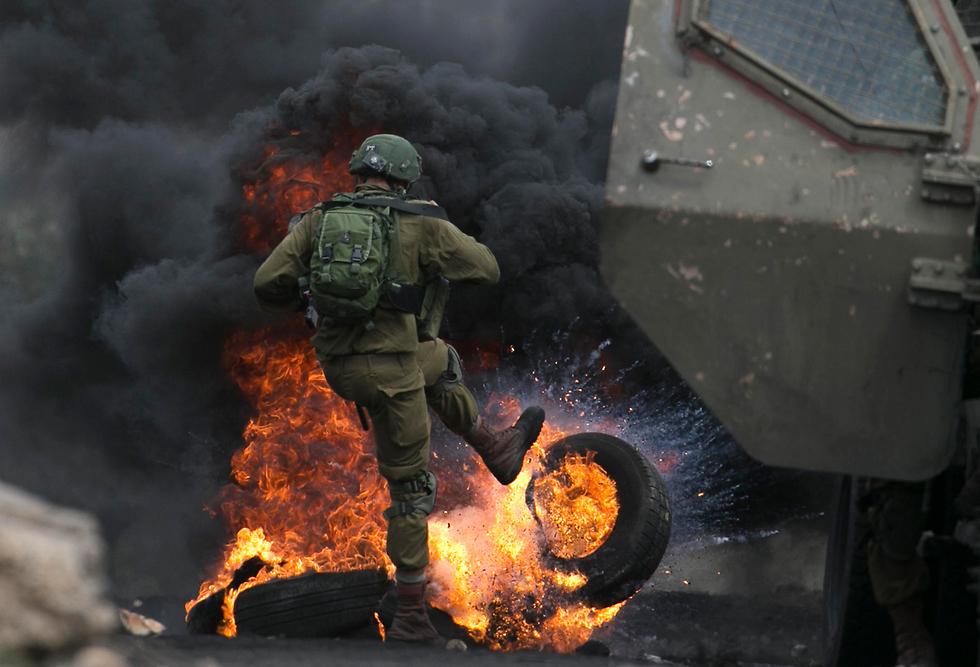 חייל מפנה צמיגים בוערים מהכביש בעימותים ליד שכם (צילום: AFP)