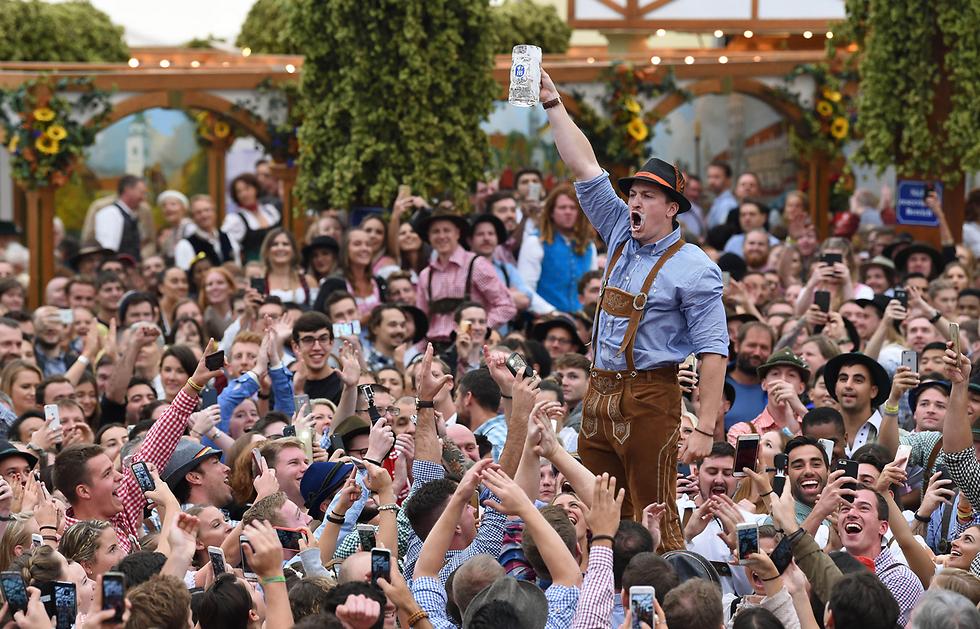 """מרימים כוס בירה בפסטיבל """"אוקטוברפסט"""" במינכן (צילום: AFP)"""