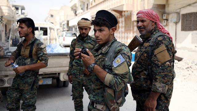 """טוענים שמשטר אסד ובעלי בריתו פוגעים במאמציהם נגד דאעש. לוחמי ארגון """"הכוחות הסוריים הדמוקרטיים"""" באזור א-רקה (צילום: רויטרס) (צילום: רויטרס)"""