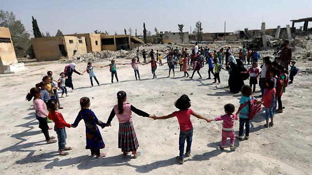 תלמידי בית ספר משחקים בין ההריסות בחלב (צילום: רויטרס) (צילום: רויטרס)
