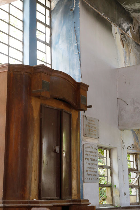 ארון הקודש הפרוץ ולימינו לוחות ההנצחה לרב נפתלי גמרא ולרוכש המגרש ומייסד בית הכנסת, שמעיה קרייזבוים  (צילום: עמרי טלמור)