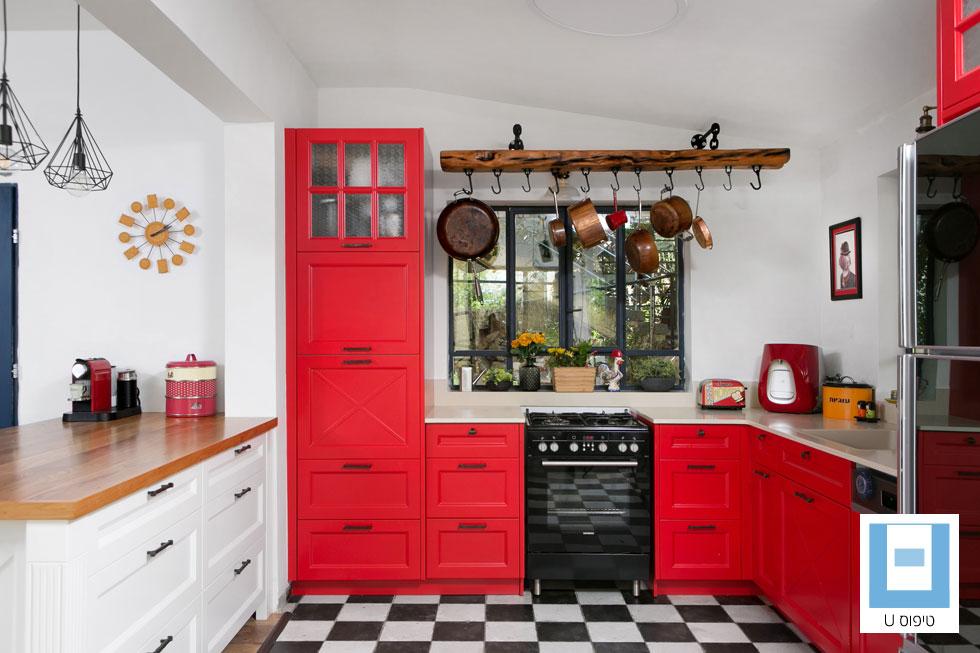 מטבח של 20 מ''ר בבית בן 230 מ''ר, בעיצוב אלה מורגן. הארונות תוכננו לפי חלונותיו של הבית ישן, ובשיפוץ נהרס קיר שהפריד בין המטבח לכניסה, ובמקומו נבנה אי גדול לאחסון. זהו יתרונו הגדול של מטבח בצורת U - הוא פתוח וידידותי, ומאפשר הרבה שטחי אחסון (צילום: שירן כרמל)