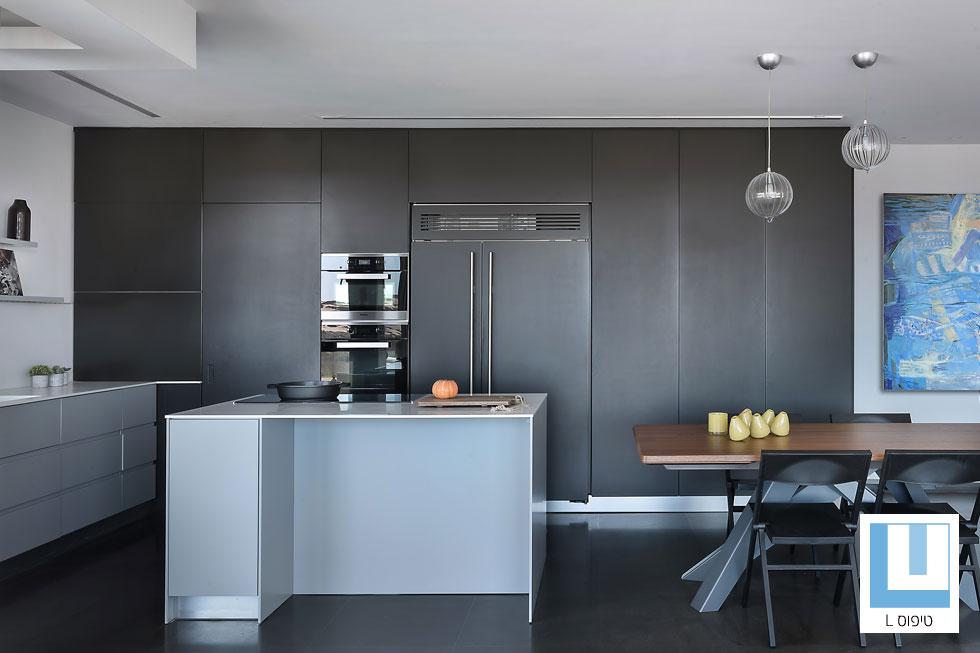 מטבח של 20 מ''ר בדירת 150 מ''ר, בעיצובה של מיכל האן, שמתחה את הארונות הגבוהים לכיוון פינת האוכל, כך שהם הפכו לרהיט משמעותי (צילום: עמית גושר)