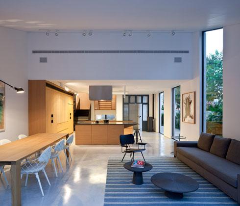 מטבח של 24 מ''ר בבית בן 240 מ''ר, בתכנון לוי-חמיצר. המקבילים הם שני איים מעץ עם משטחי עבודה שחורים (צילום: עמית גרון)