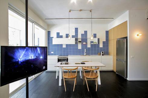 מטבח של 13 מ''ר בדירת 90 מ''ר, בעיצוב דורי רדליך. מעל הארונות הנמוכים ארון קלפה לבן ומדף פתוח מברזל דקיק (צילום: עדי כהן צדק)