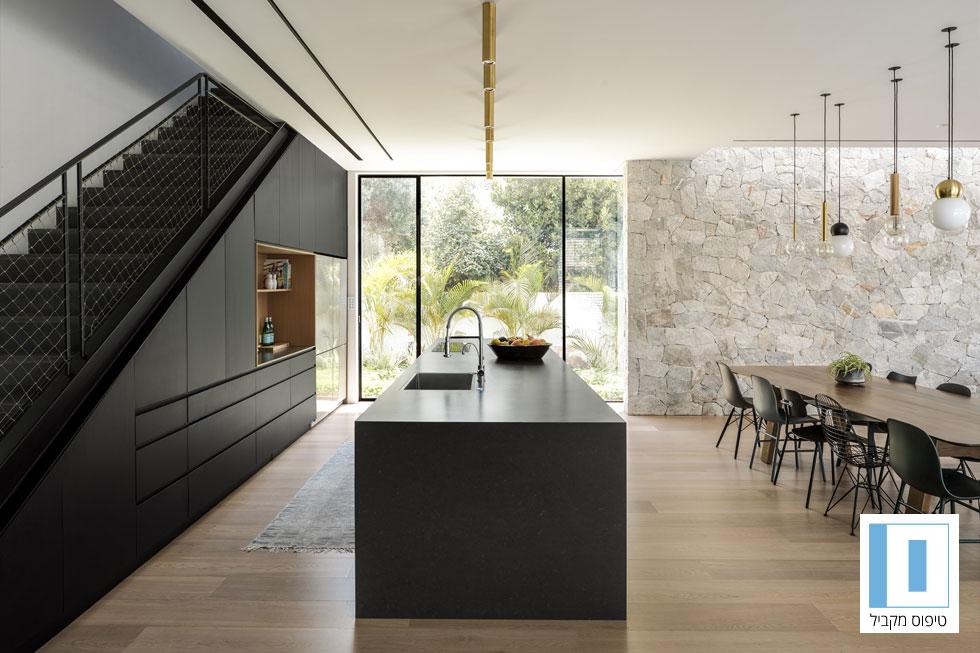 מטבח של 18 מ''ר בבית בן 320 מ''ר, בעיצוב הדס פרידלר. מטבח בקווים מקבילים הוא הבחירה המועדפת על אדריכלים ומעצבי פנים - צלע של ארונות גבוהים על הקיר ואי מלפנים - אך היא דורשת מרחב לארונות עמוקים ואי גדול. כאן הותקנו הארונות מתחת לגרם המדרגות, כדי לנצל את השטח לאחסון אופטימלי (צילום: עידו אדן)