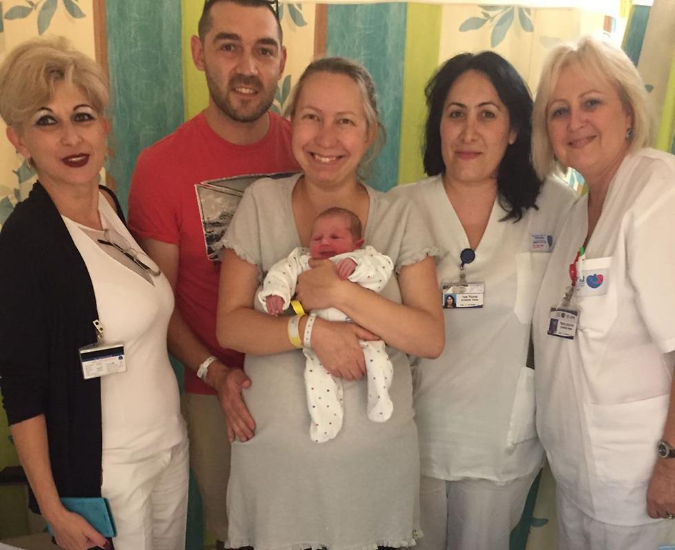 יוליה ודניס עם בתם הבכורה והצוות הרפואי ()