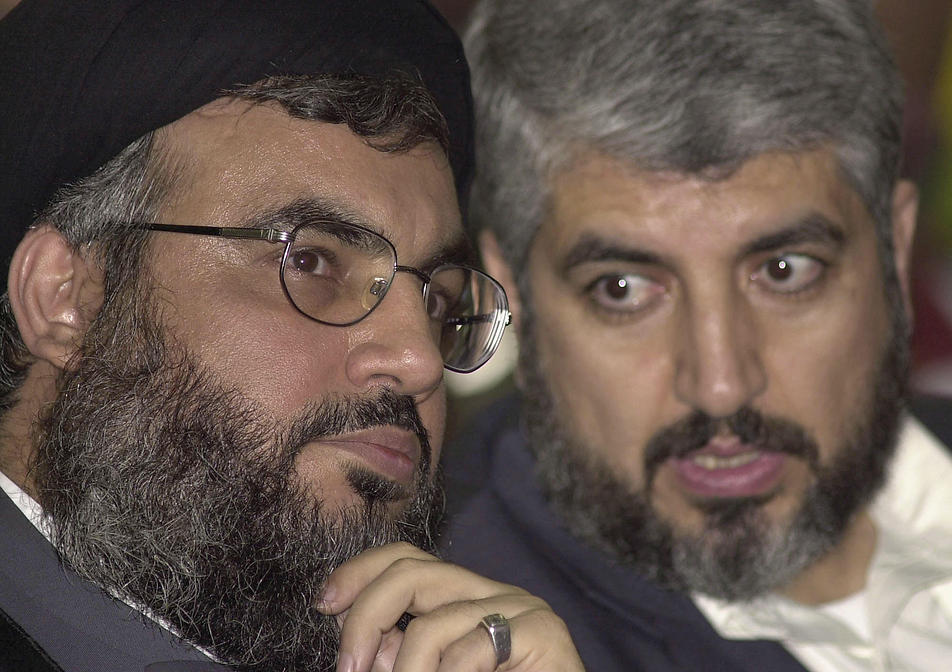 March 27, 2004: Hezbollah leader Hassan Nasrallah (L) chats with Khaled Mashaal, head of Hamas' political bureau, during a Hezbollah rally marking the assassination of Hamas founder Sheik Ahmed Yassin in Beirut, Lebanon (Photo: AP)