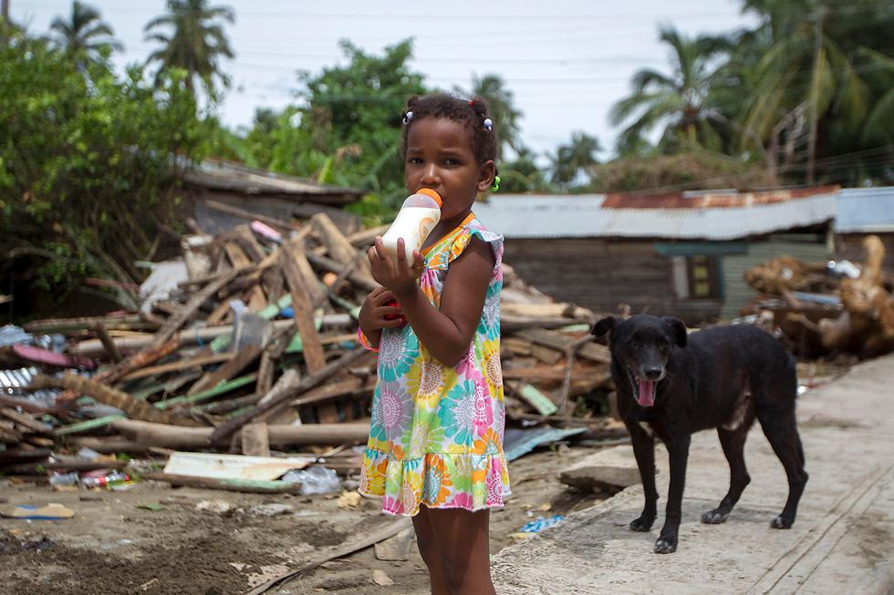 """ילדה ליד בית שנהרס בהוריקן """"מריה"""" ברפובליקה הדומיניקנית (צילום: AFP)"""