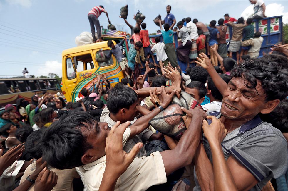 פליטים בני רוהינגה נאבקים על חומרי הסיוע המחולקים להם בבנגלדש (צילום: רויטרס)