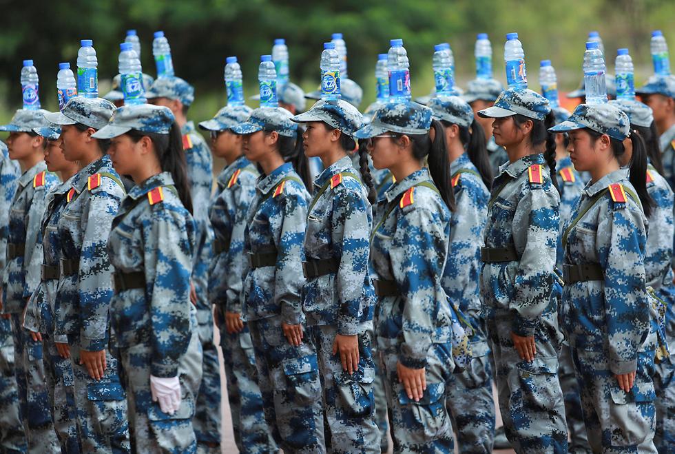 סטודנטים מאזנים בקבוקי מים על ראשיהם באימון בסגנון צבאי באוניברסיטה בננינג, סין (צילום: רויטרס)
