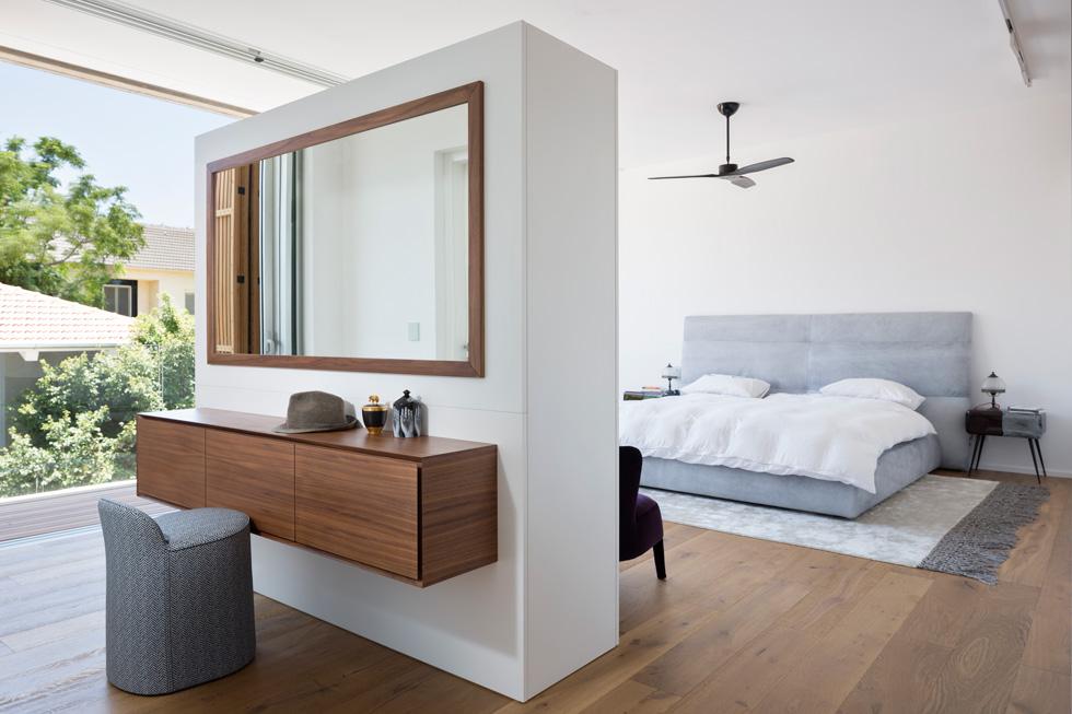 בכניסה לחדר השינה קיר נמוך המפריד בין המיטה לחדר הרחצה. מצד אחד של הקיר פינת איפור, מצדו השני, מול המיטה, תלוי מסך טלוויזיה (צילום : שי אפשטיין)